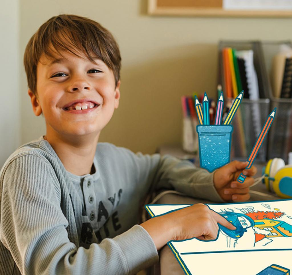 Photo of Ethan smiling while colouring in a drawing