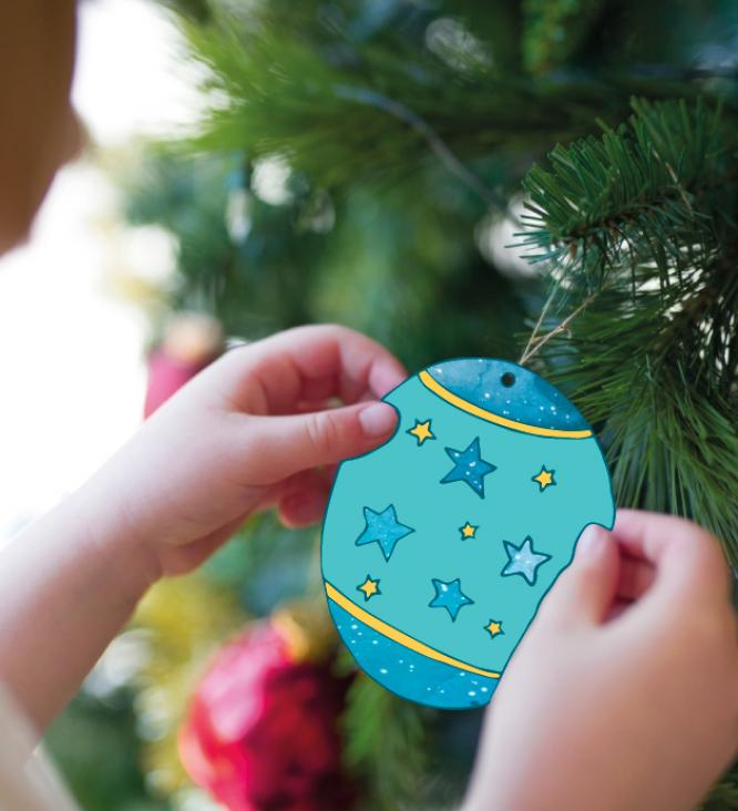child placing a decoration on a christmas tree